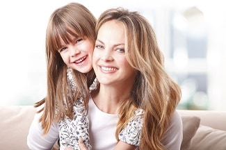 Close-up portrait of beautiful blond hair mother having fun with her cute daughter. Little girl and her mum hugging each other while sitting at sofa.